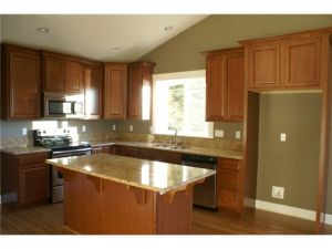 The large kitchen features slab granite counters, stainless stee
